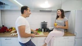 Lyckliga par som tillsammans lagar mat i köket långsam rörelse stock video