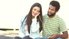 Lyckliga par som tillsammans lyssnar till musik och att dela hörlurar stock video