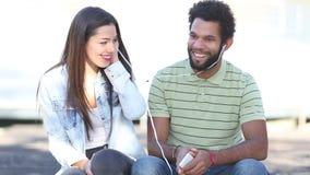 Lyckliga par som tillsammans lyssnar till musik och att dela hörlurar arkivfilmer