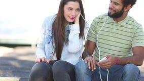 Lyckliga par som tillsammans lyssnar till musik och att dela hörlurar lager videofilmer