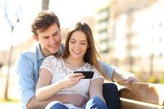 Lyckliga par som tillsammans lyssnar till musik på en bänk arkivbilder