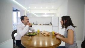 Lyckliga par som tillsammans pratar och har frukosten hemma i köket arkivfilmer