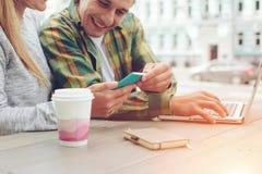 Lyckliga par som tillsammans spenderar tid i kafét, rengöringsduk som surfar och håller ögonen på roliga bilder på telefonen royaltyfri foto