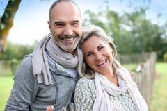 Lyckliga par som tillsammans står i bygd Royaltyfria Foton