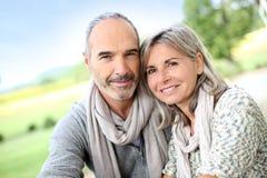 Lyckliga par som tillsammans står i fält Arkivfoto