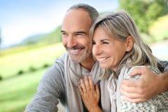 Lyckliga par som tillsammans står i fält Royaltyfri Foto