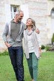 Lyckliga par som tillsammans står i trädgård Royaltyfri Fotografi