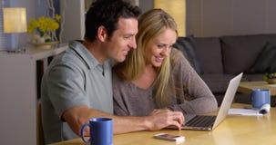 Lyckliga par som tillsammans surfar internet Arkivfoto