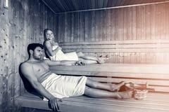 Lyckliga par som tillsammans tycker om bastun på brunnsorten arkivfoton