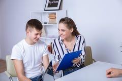Lyckliga par som tillsammans undertecknar ett avtal p? royaltyfria foton