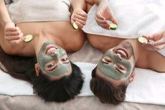 Lyckliga par som tycker om ansikts- behandlingtillv?gag?ngss?tt i brunnsortsalong arkivbild