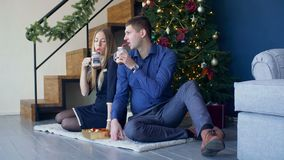 Lyckliga par som tycker om den varma drinken under julträd lager videofilmer