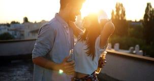 Lyckliga par som tycker om drinkar och balkongen Arkivfoto