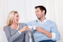 Lyckliga par som tycker om en kopp te eller ett kaffe Royaltyfri Foto