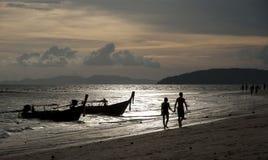 Lyckliga par som tycker om en strand, går på den romantiska solnedgången Royaltyfri Foto