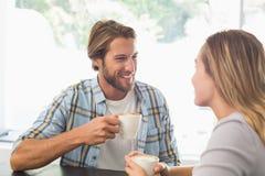 Lyckliga par som tycker om ett kaffe Arkivbilder