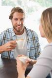 Lyckliga par som tycker om ett kaffe Arkivfoto