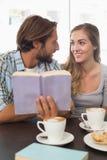Lyckliga par som tycker om ett kaffe som läser en bok Royaltyfri Foto