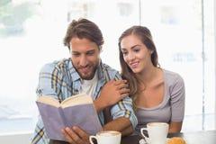 Lyckliga par som tycker om ett kaffe som läser en bok Arkivbild