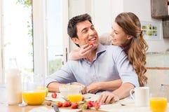 Lyckliga par som tycker om frukosten Fotografering för Bildbyråer