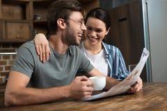 Lyckliga par som tycker om frukosten med kaffe och tidningen royaltyfri fotografi