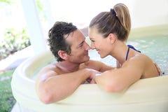 Lyckliga par som tycker om i bubbelpool Royaltyfria Foton