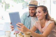 Lyckliga par som tycker om kaffe genom att använda minnestavlan Royaltyfria Foton