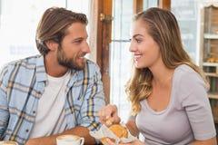 Lyckliga par som tycker om kaffe och kakan Royaltyfri Fotografi