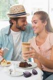 Lyckliga par som tycker om kaffe och kakan Royaltyfria Bilder