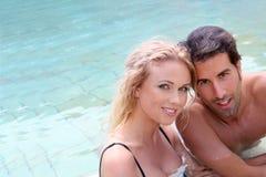 Lyckliga par som tycker om pölen Fotografering för Bildbyråer