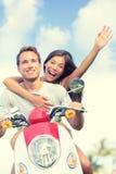 Lyckliga par som tycker om sparkcykelritt mot himmel Arkivbild