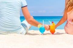 Lyckliga par som tycker om tropiska coctailar på sandstranden Arkivfoto
