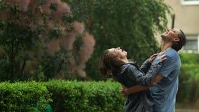 Lyckliga par som tycker om varmt sommarregn som spenderar Tid tillsammans i staden, parkerar utomhus arkivfilmer