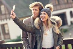 Lyckliga par som utomhus går i vinter arkivfoto