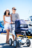 Lyckliga par som utomhus går med behandla som ett barn arkivfoton