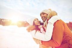 Lyckliga par som utomhus kramar i vinter Arkivbild