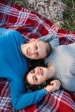 Lyckliga par som utomhus ligger på plädet arkivfoto