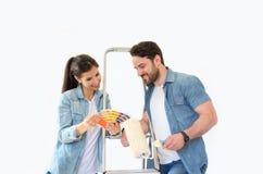 Lyckliga par som väljer färger för garnering som målar det nya huset fotografering för bildbyråer