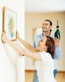 Lyckliga par som väljer stället för bild i ram Fotografering för Bildbyråer