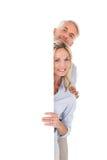 Lyckliga par som visar den stora affischen Royaltyfri Fotografi