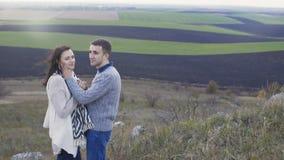 Lyckliga par står på vaggar, handlag och kyssar i blåsig dag 4K stock video