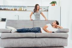 Lyckliga par talade i vardagsrummet fotografering för bildbyråer