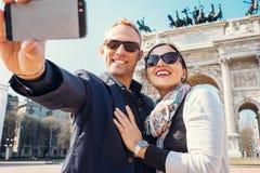 Lyckliga par tar ett selfiefoto på bågen av fred i Milan Arkivbilder