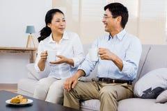 Lyckliga par tillsammans på soffan Royaltyfri Bild