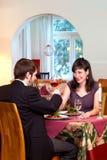 Lyckliga par tycker om romantisk matställe Arkivfoton