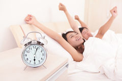 Lyckliga par vaknar upp i säng Arkivfoton