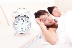 Lyckliga par vaknar upp i säng Royaltyfri Bild