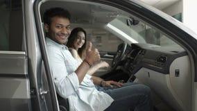 Lyckliga par visar tummar upp i kabin för bil` s lager videofilmer