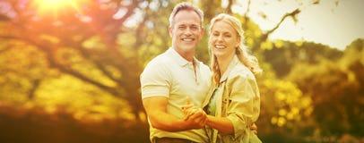 Lyckliga parinnehavhänder mot träd royaltyfria bilder