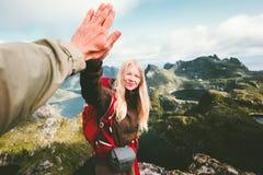 Lyckliga parvänner som ger fem händer som fotvandrar i berg fotografering för bildbyråer